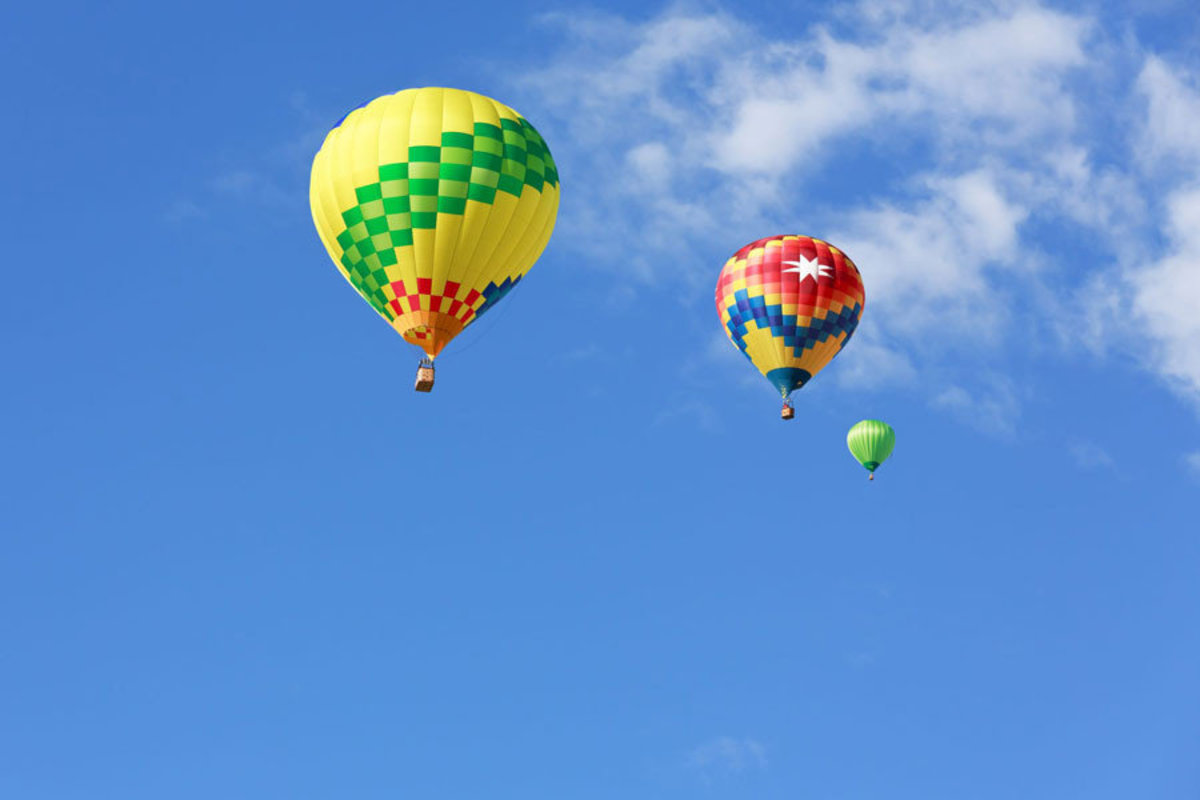 Colorful hot air balloons sail across the sky on a summer day Additional Thumbnail