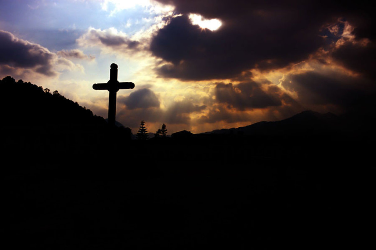 A cross is silhouetted by rays of light that break through an overcast day Additional Thumbnail