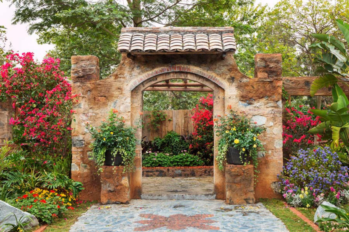 stone doorway leads into a lush, colorful garden with a variety of flowers and plants Additional Thumbnail