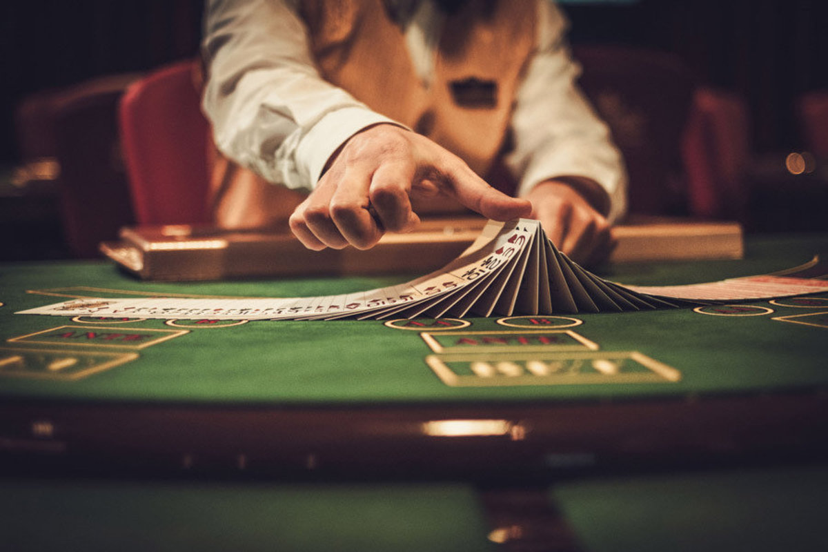Lucky cards casino croupier shows off his card skills before you on this gambling table Additional Thumbnail