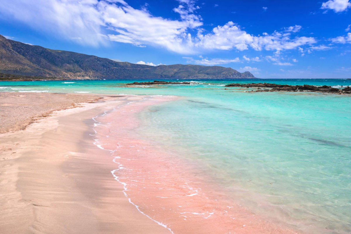 Glistening teal waters of the ocean lap up onto Elafonissi Beach's famous pink-tinged sand Sample
