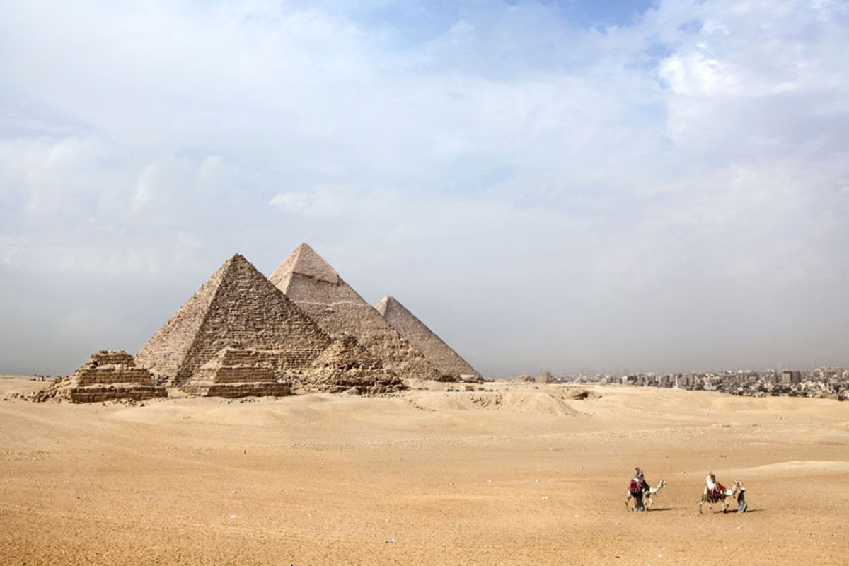 Two camel riders cross the desert sands in front of the Giza Pyramids