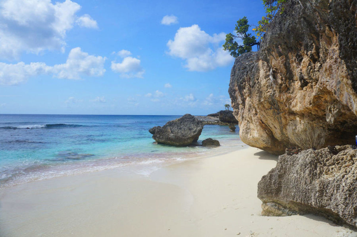 a romantic tranquil scene featuring soft sand, gentle waves and a naturally textured rock wall