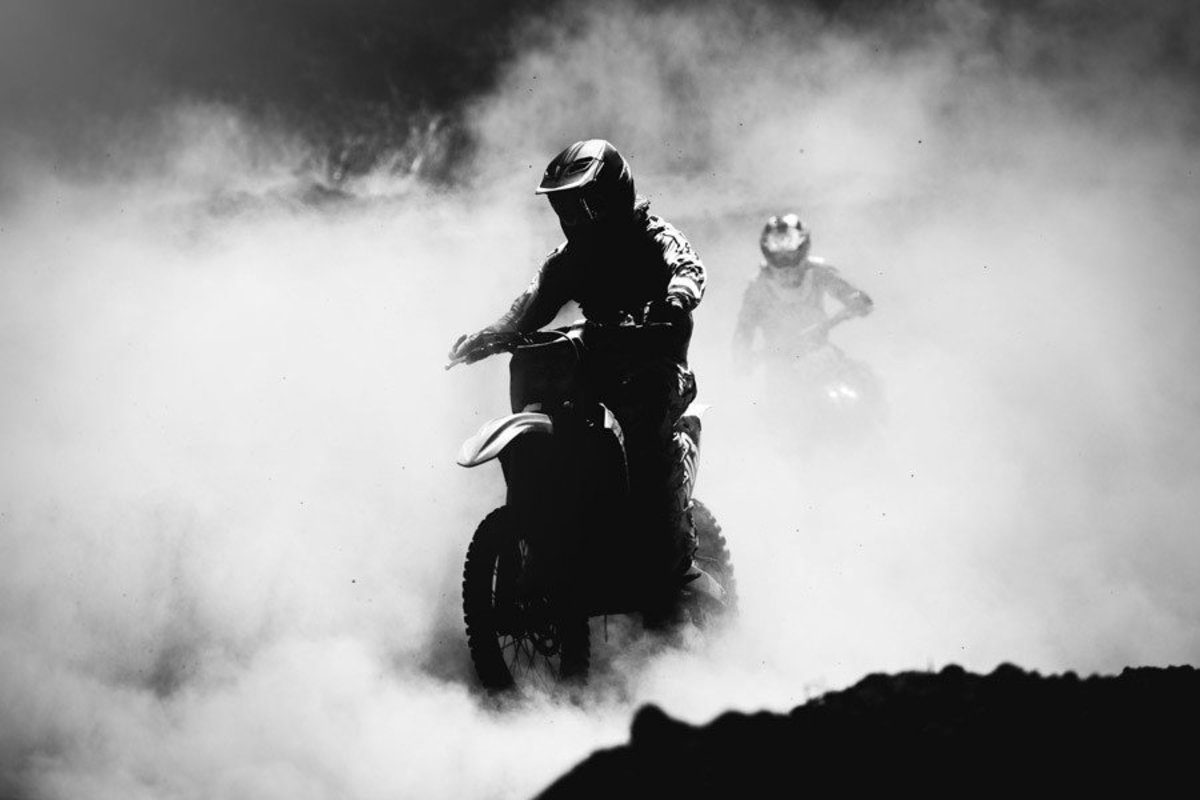two motorbike racers emerging from kicked up smoke and dirt Additional Thumbnail