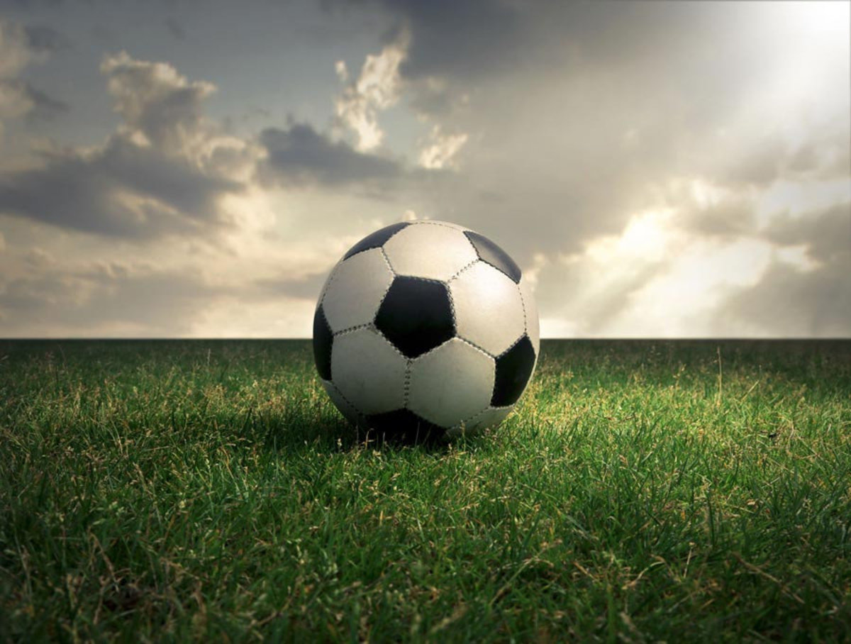 sun shines down on a soccer ball in a field Additional Thumbnail