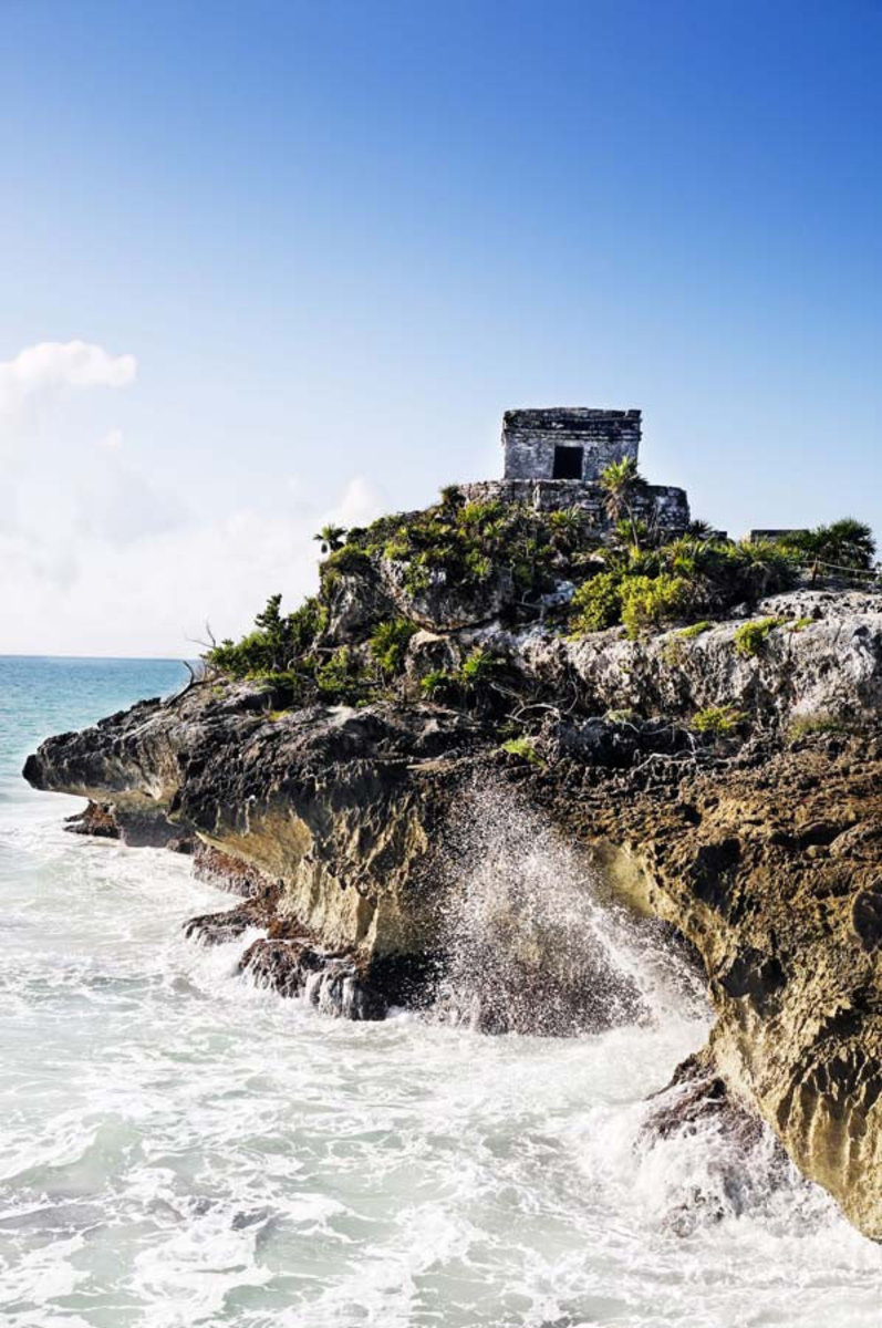 Waves crash upon the rugged shore of the Mayan archeologic site of Tulum